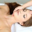 Beautiful young woman during facial massage in cosmetic salon close up — Stock Photo #33019893
