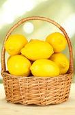 Limões maduros na cesta de vime na mesa no fundo brilhante — Foto Stock
