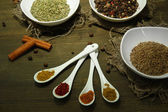 Assortment of spices in white spoons and bowls, on wooden background — Stock Photo