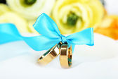 Wedding rings tied with ribbon on white fabric — Fotografia Stock