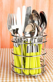 Knives, forks and spoons in metal stand on tablecloth on orange background — Stock Photo