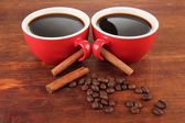 Red cups of strong coffee and coffee beans on wooden background — Stock Photo