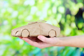 Mano de mujer sosteniendo un coche envuelto en papel kraft marrón, sobre fondo de naturaleza — Foto de Stock