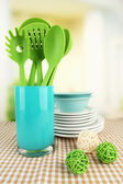 Plastic kitchen utensils in stand with clean dishes on tablecloth on bright background — Stock Photo