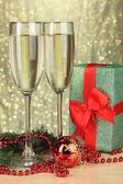 Copos de champanhe com caixa de presente no fundo brilhante — Foto Stock