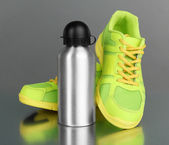 Sports bottle and sneakers on grey background — Foto de Stock