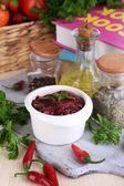 Raw liver in bowl with spices and condiments on wooden table close-up — Stock Photo