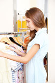 Beautiful girl chooses clothes on hangers on room background — Stock Photo