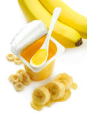 Tasty dessert in open plastic cup and banana, isolated on white — Stock Photo
