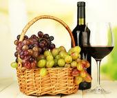 熟したブドウ枝編み細工品バスケット、ボトル、明るい背景にワインのガラス — ストック写真