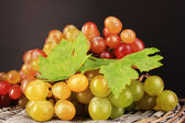 Ripe sweet grape on wooden table, on grey background — Stock Photo