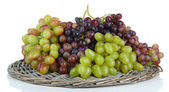 Fresh grape on wicker mat isolated on white — Stock Photo