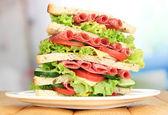 Sanduíche enorme na mesa de madeira, no fundo brilhante — Foto Stock