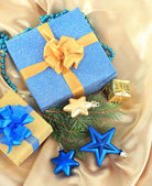 Beautiful bright gifts and christmas decor, on silk cloth — Stock Photo