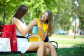 Two beautiful young woman with shopping bags in park — Stockfoto