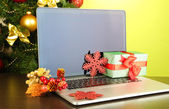 Laptop with gifts on table on green background — Stock Photo
