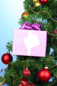Gift on Christmas tree on color background — ストック写真