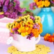 Bouquet of marigold flowers in watering can on wooden table on natural background — Stock Photo #33083939