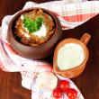 Potato pancakes in pot, on wooden background — Stock Photo #33084339