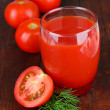 Tomato juice in glass, on wooden background — Stock Photo #33084413