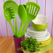 Plastic kitchen utensils in stand with clean dishes on table on wooden background — Stock Photo #33084937