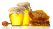Sweet honeycombs, wooden drizzler, and jars with honey, isolated on white — Stock Photo