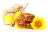Sweet honeycombs, jars with honey, wooden drizzler and sunflower, isolated on white — Stock Photo