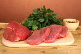Raw beef meat with spices on wooden table on brown background — Stock Photo