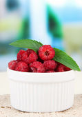 Fresh raspberry on wooden table, on bright background — Stock Photo
