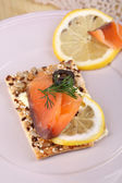 Salmon sandwich on plate on wooden table close-up — Stockfoto
