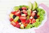 Fruit salad in plate on napkin wooden table — Stock Photo
