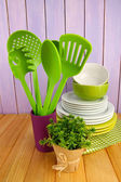 Plastic kitchen utensils in stand with clean dishes on table on wooden background — Stock Photo