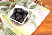 Olives in bowl with branch on napkin on wooden board on table — Foto Stock
