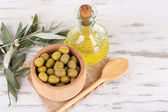Olive oil and olives in bowl on sackcloth wooden table — Foto Stock