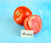 Calorie content of tomato on wooden table close-up — Stock Photo