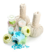Aromatic salts in glass bottles and herbal compress balls for spa treatment, isolated on white — Stock Photo