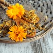Fresh and dried calendula flowers on wooden background — Stock Photo #33175713
