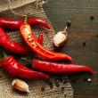 Red hot chili peppers and garlic, on sackcloth, on wooden background — Stock Photo