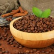 Coffee beans in bowl on wooden background — Stock Photo