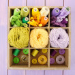 Multicolored skeins of thread and buttons in box closeup — Foto Stock