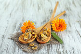 Fresh and dried calendula flowers on wooden background — Stock Photo