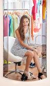 Hermosa chica trata de zapatos cerca de espejo en el fondo de la habitación — Foto de Stock