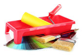 Roller, brushes and bright palette of colors isolated on white — Stock Photo