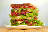 Huge sandwich on wooden table, on light background — Stock fotografie