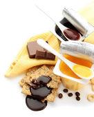 Heerlijke desserts in open plastic bekers en honing kammen, vruchten en vlokken op servet, geïsoleerd op wit — Stockfoto