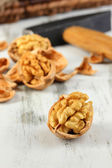 Broken walnuts with hammer on wooden table close-up — Stock Photo