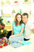 Happy young couple near Christmas tree at home — Stock fotografie