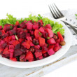 Beet salad on plate on napkin on wooden board isolated on white — Stock Photo #33180509