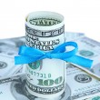 Dollars with gift bow on white background — Stock Photo