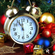 Alarm clock with Christmas tree and decoration on table on blue background — Stock Photo